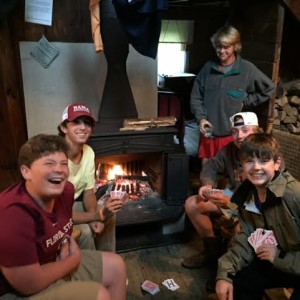 Some of the crew enjoys cards around the stove while the rain falls outside.